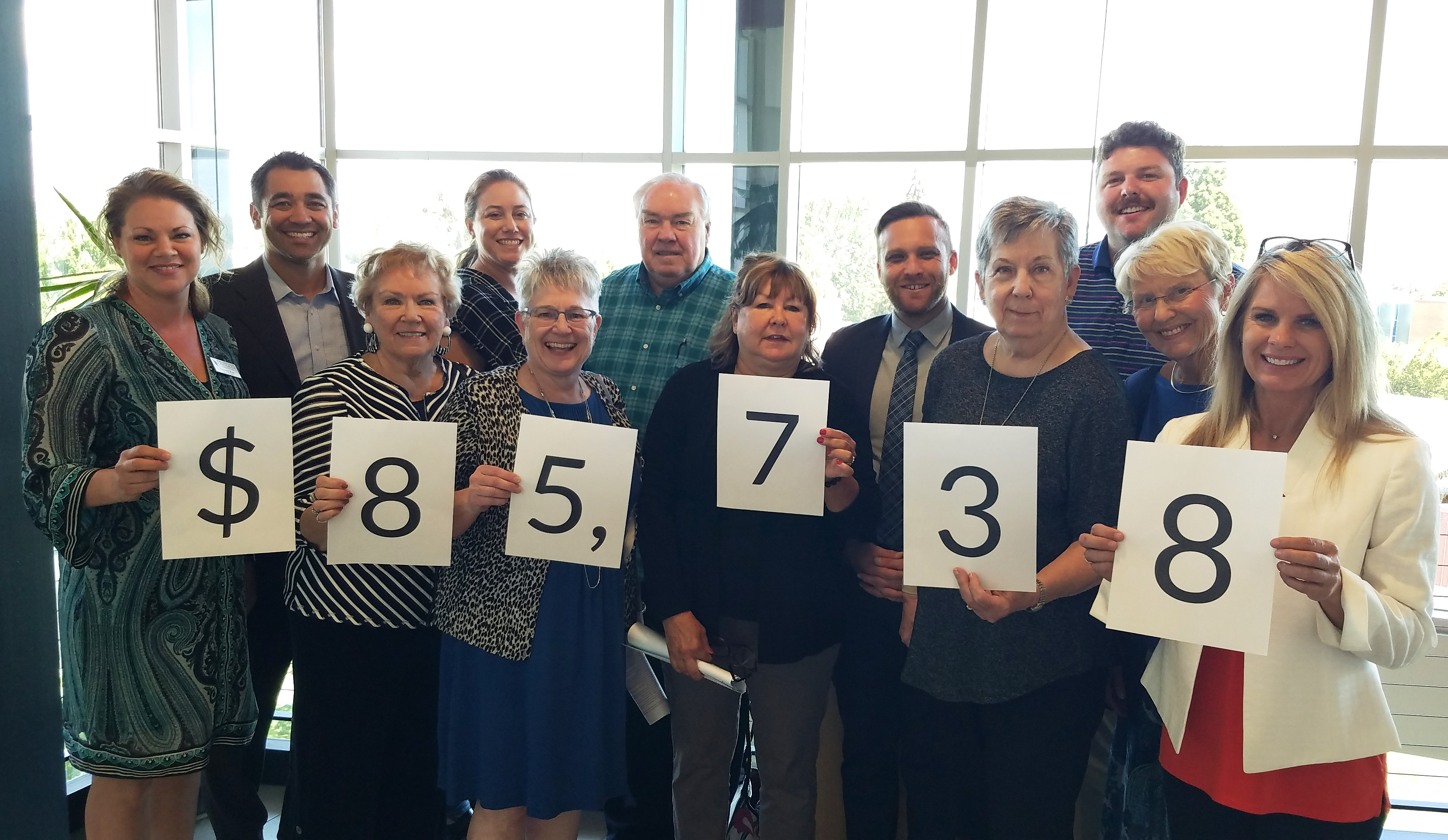 The Wenatchee Valley College Foundation Board holds up papers with the total amount raised written on them